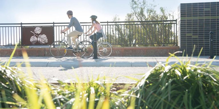 Couple riding their bicycles at pedestrian pathway in Haynes where Move Homes offers affordable house and land packages for new home buyers in Perth