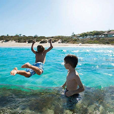 Kids jumping into Lagoon ocean at Yanchep where Move Homes offers affordable house and land packages for new home buyers in Perth